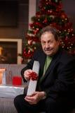Hombre mayor que envuelve presentes en la Navidad Fotografía de archivo