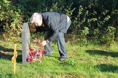 Hombre mayor que está de luto en un cementerio. Foto de archivo libre de regalías