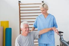 Hombre mayor que estira con su terapeuta Foto de archivo