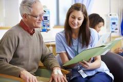 Hombre mayor que experimenta la quimioterapia con la enfermera Imagen de archivo libre de regalías