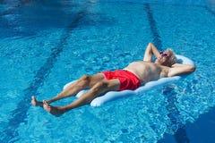 Hombre mayor que flota en el agua Imagen de archivo libre de regalías