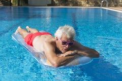 Hombre mayor que flota en el agua Fotos de archivo