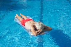 Hombre mayor que flota en el agua Foto de archivo libre de regalías