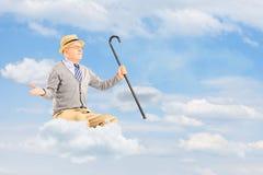 Hombre mayor que flota en una nube y brazos de extensión contra nublado Imágenes de archivo libres de regalías