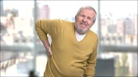 Hombre mayor que frota el suyo más de espalda almacen de metraje de vídeo