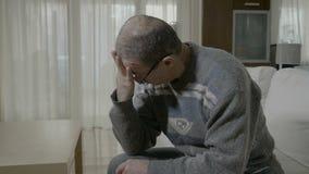 Hombre mayor que frota sus templos que sufren de dolor de cabeza intenso en casa - metrajes