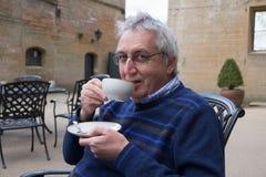 Hombre mayor que goza de la taza de puertas del té o del café hacia fuera Imagen de archivo libre de regalías