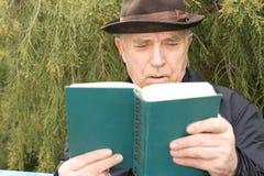 Hombre mayor que goza de su novela imagenes de archivo