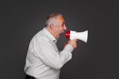 Hombre mayor que grita usando el megáfono Foto de archivo libre de regalías