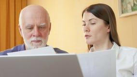 Hombre mayor que habla con el consejero financiero Cliente mayor de explicación del consultor femenino su plan de jubilación almacen de metraje de vídeo