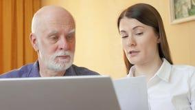 Hombre mayor que habla con el consejero financiero Cliente mayor de explicación del consultor femenino su plan de jubilación almacen de video
