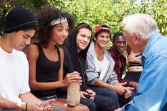Hombre mayor que habla con la cuadrilla de gente joven foto de archivo