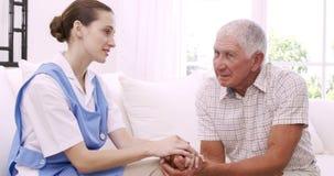 Hombre mayor que habla con la enfermera almacen de metraje de vídeo