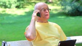 Hombre mayor que habla en el teléfono elegante metrajes