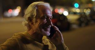 Hombre mayor que habla en el teléfono móvil en la ciudad 4k almacen de video