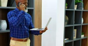 Hombre mayor que habla en el teléfono móvil mientras que usa el ordenador portátil 4k almacen de metraje de vídeo