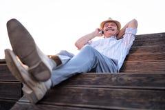 Hombre mayor que habla en la reclinación del teléfono fotografía de archivo