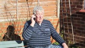Hombre mayor que habla en un teléfono móvil almacen de video