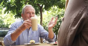 Hombre mayor que habla mientras que comiendo el café 4k almacen de video