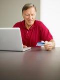 Hombre mayor que hace compras en línea Imagen de archivo libre de regalías
