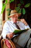 Hombre mayor que hace crucigrama Foto de archivo libre de regalías