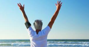 Hombre mayor que hace ejercicio en la playa