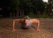 Hombre mayor que hace flexiones de brazos Foto de archivo libre de regalías