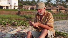 Hombre mayor que hace la flauta por las manos al aire libre almacen de metraje de vídeo