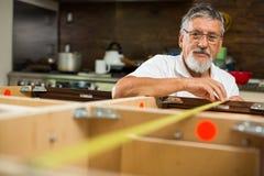 Hombre mayor que hace poniendo juntos a los armarios de cocina imagen de archivo