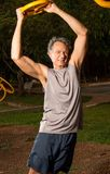 Hombre mayor que hace posiciones en cuclillas al aire libre Imagen de archivo libre de regalías