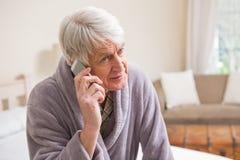 Hombre mayor que hace una llamada de teléfono en cama Fotografía de archivo libre de regalías
