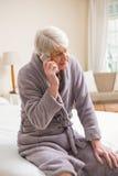 Hombre mayor que hace una llamada de teléfono en cama Imagen de archivo