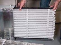 Hombre mayor que inserta un nuevo filtro de aire en un horno de la HVAC fotos de archivo