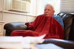 Hombre mayor que intenta guardar la manta inferior caliente en casa Foto de archivo libre de regalías