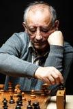 Hombre mayor que juega a ajedrez Imagen de archivo