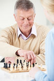 Hombre mayor que juega a ajedrez con la nieta adolescente Fotos de archivo libres de regalías