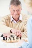Hombre mayor que juega a ajedrez con la nieta adolescente Imagen de archivo