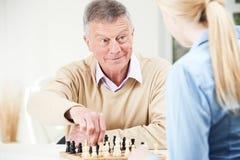 Hombre mayor que juega a ajedrez con la nieta adolescente Imagen de archivo libre de regalías
