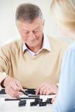 Hombre mayor que juega dominós con la nieta adolescente Fotos de archivo libres de regalías