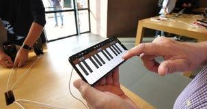 Hombre mayor que juega el piano en el iPhone XS máximo en GarageBand App almacen de metraje de vídeo