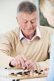 Hombre mayor que juega a inspectores con la hija adolescente Imágenes de archivo libres de regalías