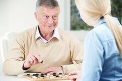 Hombre mayor que juega a inspectores con la hija adolescente Imagenes de archivo