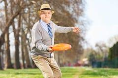 Hombre mayor que lanza un disco del disco volador al aire libre Foto de archivo libre de regalías