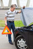 Hombre mayor que lleva a cabo la señal de peligro cerca del coche Fotos de archivo libres de regalías