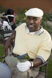 Hombre mayor que lleva a cabo la tarjeta de puntuación Fotos de archivo libres de regalías