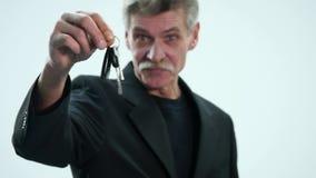 Hombre mayor que lleva a cabo llave del coche aislada en blanco almacen de video