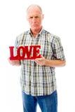 Hombre mayor que lleva a cabo un texto rojo del amor Imagen de archivo libre de regalías