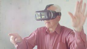 Hombre mayor que lleva gafas de la realidad virtual almacen de metraje de vídeo
