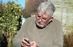Hombre mayor que manda un SMS en un móvil Imagenes de archivo