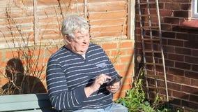 Hombre mayor que manda un SMS en un teléfono móvil almacen de metraje de vídeo